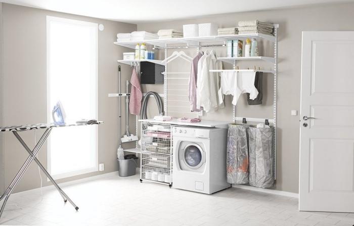 pièce aux murs beige avec plafond et plancher blanc aménagé avec table à repasser et etagere buanderie blanches