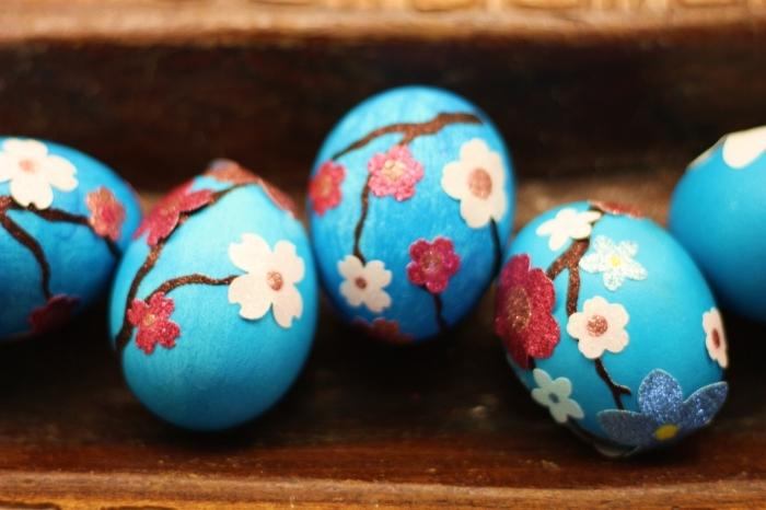 exemple oeuf a la coque avec décoration de peinture bleu clair avec fleurs et branches de papier et tissu coloré