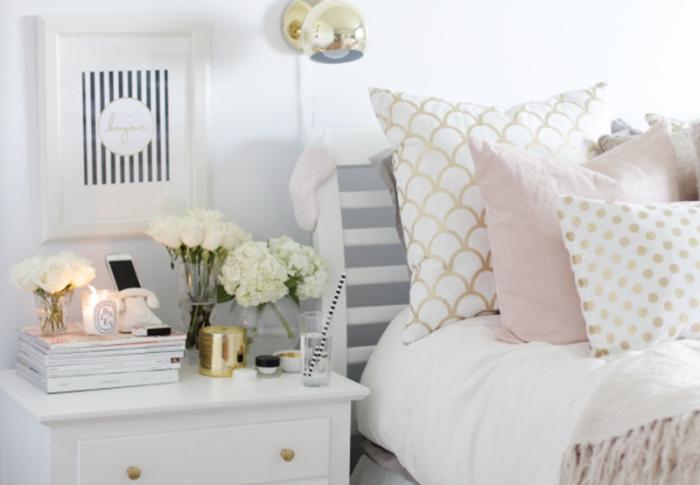 chambre blanche aménagée avec meubles de bois blanc, table de chevet blanc avec accessoires en or, housse de linge à design géométrique