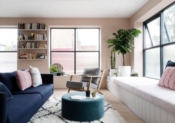 salon aux murs rose poudré avec plafond blanc et parquet de bois clair, canapé de couleur bleu foncé combiné avec tabouret turquoise