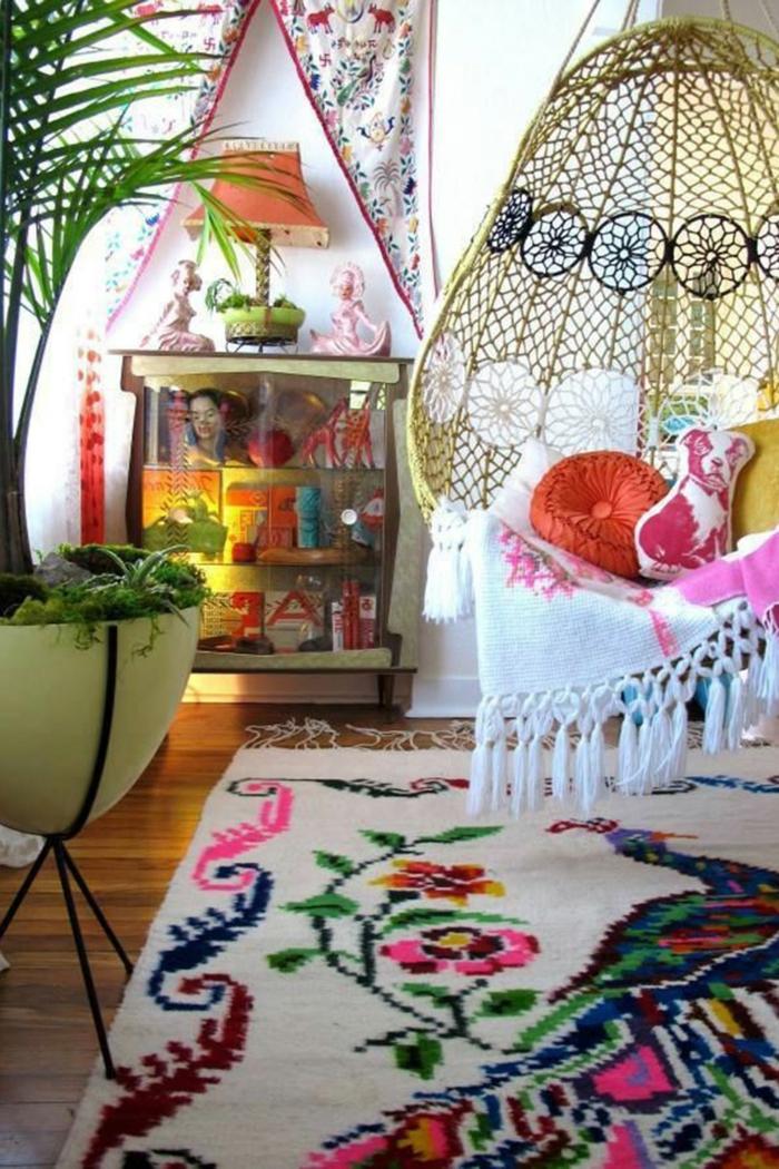 commode vintage, chaise suspendue, tapis bariolé, grand pot de fleur, peinture murale blanche
