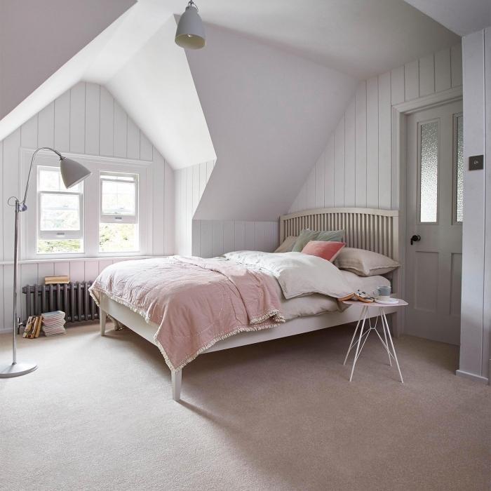 idée déco chambre à coucher sous pente aux murs blancs, déco simpliste avec grand lit à tête de bois et lampe sur pied