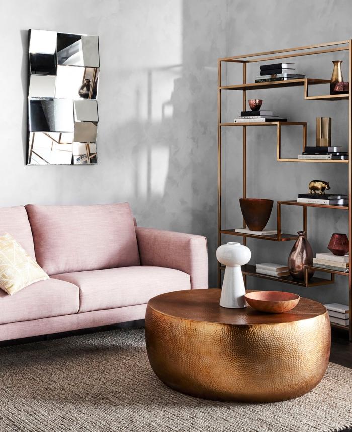 décorer un salon aux murs béton avec étagère à design cuivré de style industriel, modèle de canapé rose poudré