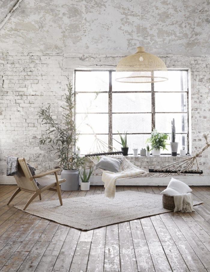esprit bohème chic avec meubles de rotin et hamac suspendue, pièce au plancher de bois et murs en papier peint briques blanches