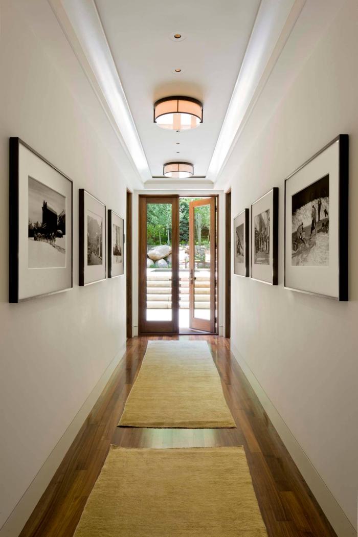 comment decorer un couloir long et étroit aux murs blancs et plancher de bois foncé avec peintures blanc et noir en cadre noir