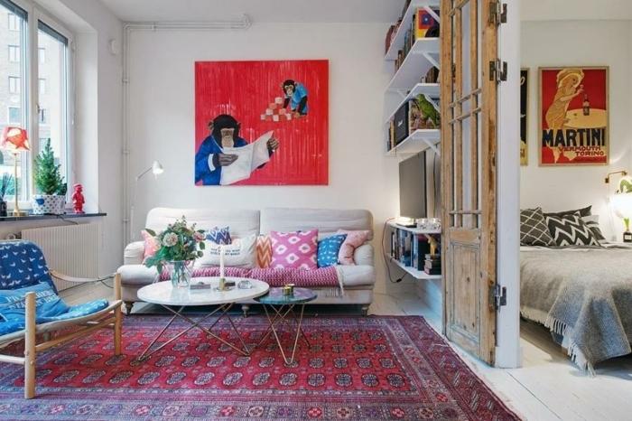 table blanche ronde, tapis boheme, chaise en bois et textile, peintures originales, bibliothèque murale