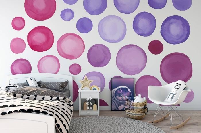 idée déco chambre d'enfant avec tapis rond gris et lit blanc, revêtement mural en papier peint blanc à cercles violet et rose