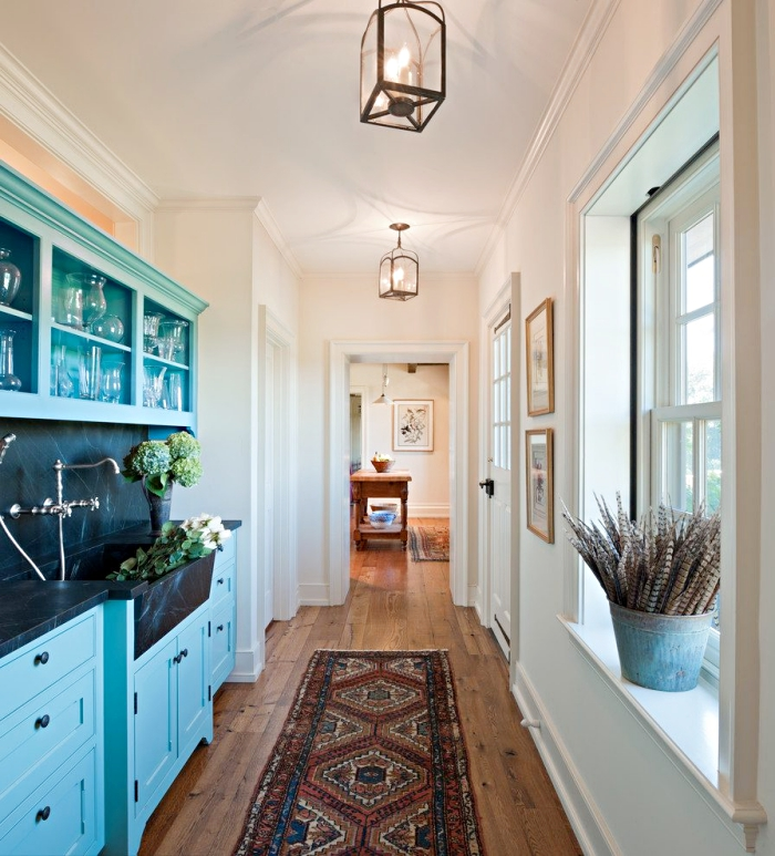style campagne et rétro dans un couloir et cuisine ouverte avec équipement de nuance bleu et murs peints en blanc