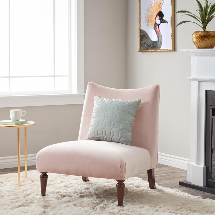 salon aux murs beige avec fauteuil de couleur rose poudré installé sur un tapis moelleux blanc, vase et cadre photo à finition cuivré