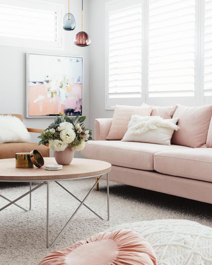 déco de salon aux murs blancs avec canapé rose poudré et table ronde basse de bois, suspension luminaire en verre