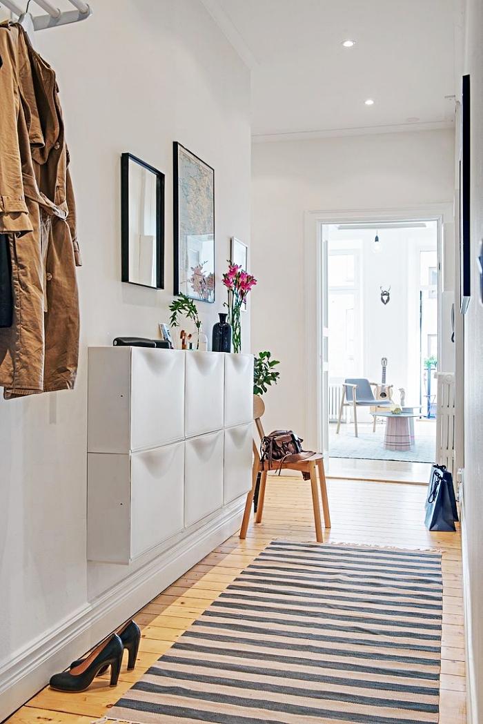 aménagement de couloir aux murs blancs avec meubles modernes, cadres photos noirs sur murs blancs et porte-manteau à design métallique