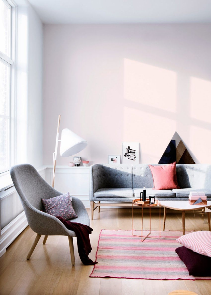 intérieur design moderne aux murs rose pale avec grande fenêtre et plafond blancs, coussins décoratifs de couleur rose et violet