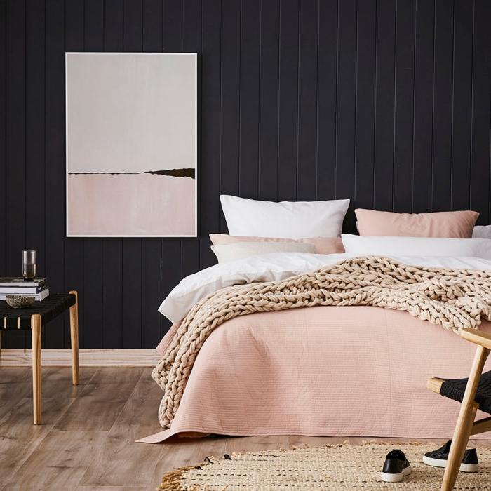 déco de chambre à coucher aux murs foncé et parquet de bois avec linge de lit rose poudré et tapis beige avec frange