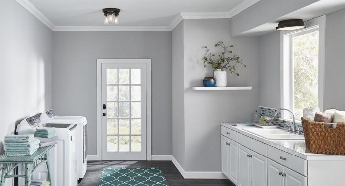 meuble buanderie de bois peint en blanc avec poignées métalliques, déco intérieur aux murs gris avec contours et meubles blancs