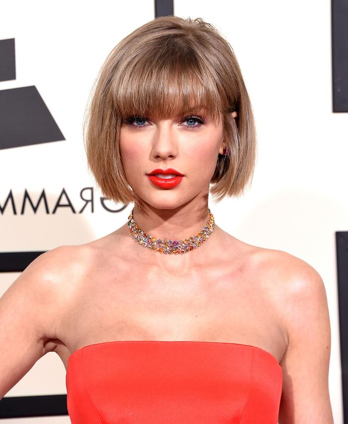frange droite sur le front et un carré court blond foncé, robe rouge, rouge a levres rouge, look tapis rouge
