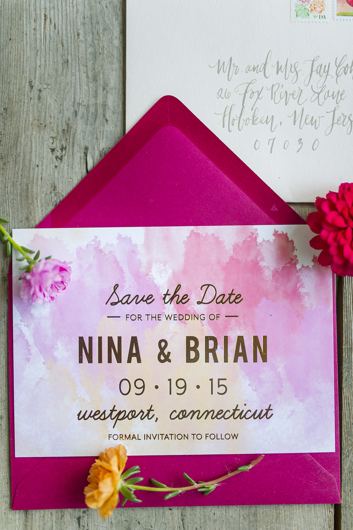un faire-part mariage chic à l'aquarelle avec un joli dégradé de couleurs et des lettres dorées, assorti avec une enveloppe couleur fuchsia