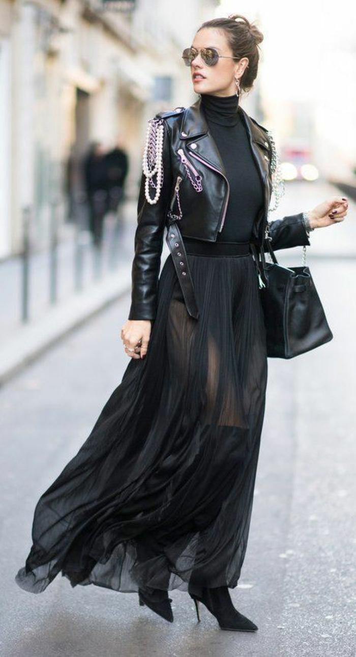 bien habillée en robe de tulle noire semi-transparent, bottines noires talons aiguilles, grand sac quotidien en noir, veste courte de rocker avec des chaînes sur l'une des épaules, pull noir moulant