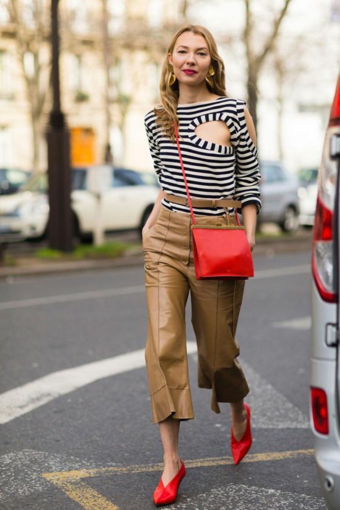 tenue chic, femme en pantalon marron clair large et court aux chevilles, top en style marin aux rayures noires et blanches, chaussures pointues rouges, ceinture fine aux rayures, sac pochette bandoulière en rouge