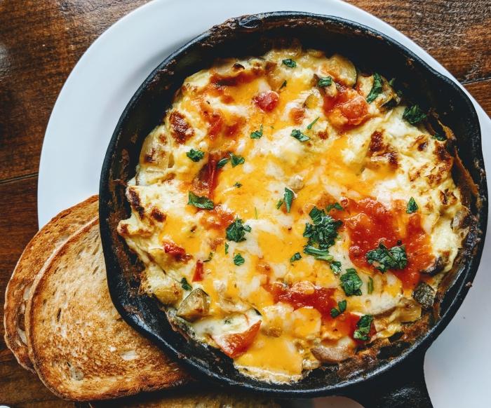 recette repas du soir rapide, préparer un diner dans poêle avec oeufs battus sauce tomate et fromage fondu