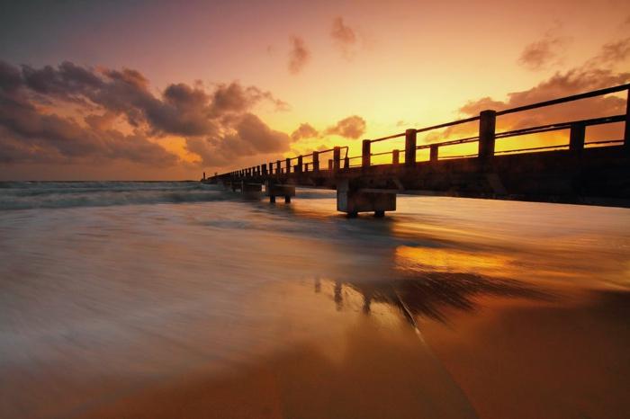 paysage de reve, pont dans la mer, ciel en orange et jaune, onde qui embrasse calmement la plage, paysage mer, iles paradisiaques