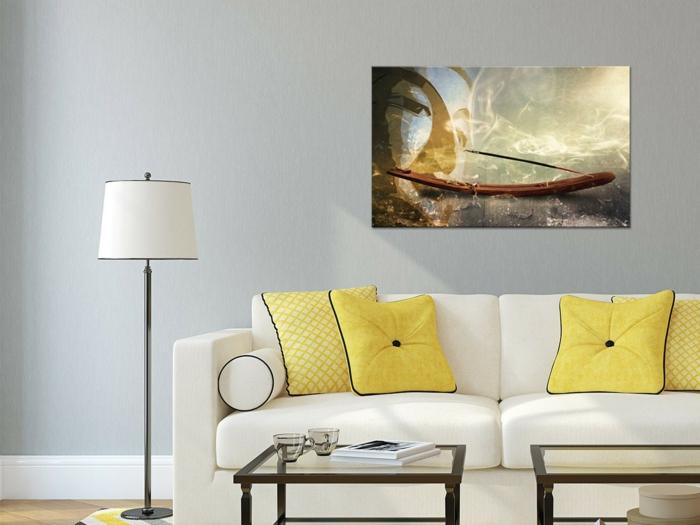 décoration feng shui, canapé en blanc avec des coussins carrés jaunes aux ourlets de tissu noir satiné, panneau décoratif avec tete de Bouddha en couleurs pastels, deux tables basses carrées en verre et en métal couleur bronze, luminaire sur pied avec abat-jour blanc et en métal noir