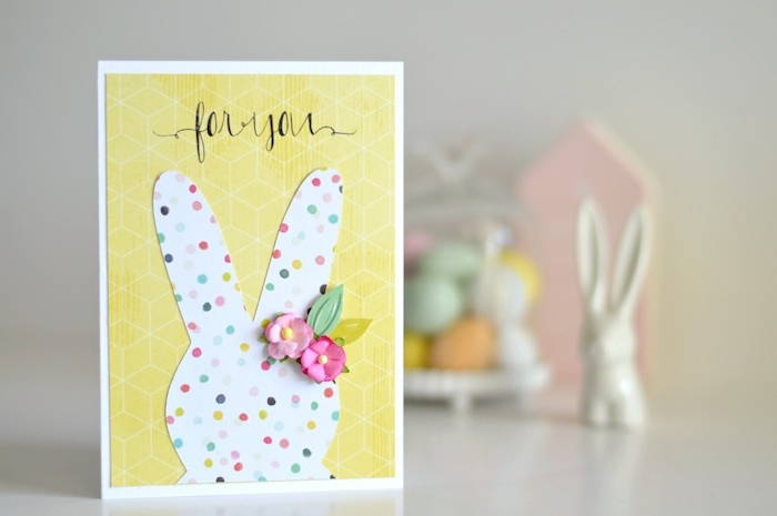 carte de paques a faire soi meme avec silhouette de lapin de paques blanc à pois colorés et fleurs artificielles sur fond jaune