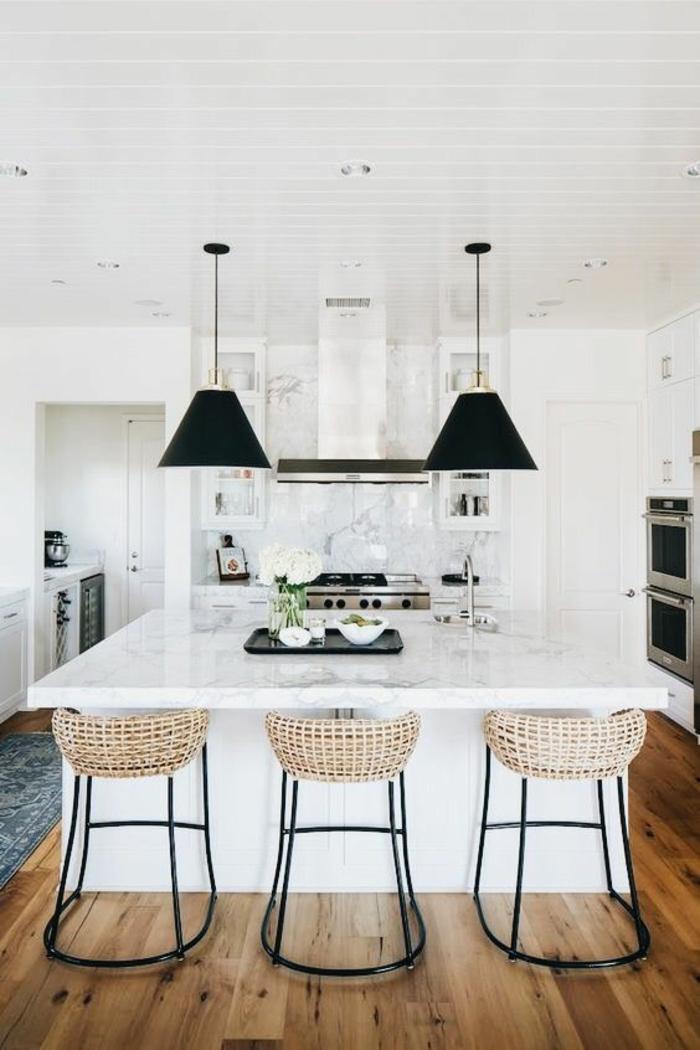 espace en noir et blanc, avec des chaises de bar en métal noir et des dossiers en rose poudré, cuisine équipée moderne, parquet en jaune et marron