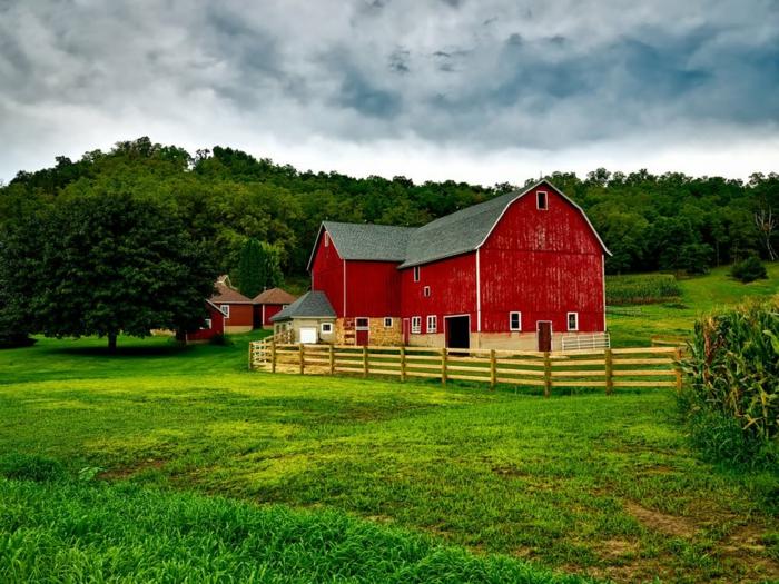 lieu paradisiaque, une maison rouge dans un champ tout vert, entourée d'arbres verts, ciel couvert de nuages gris, ambiance idyllique