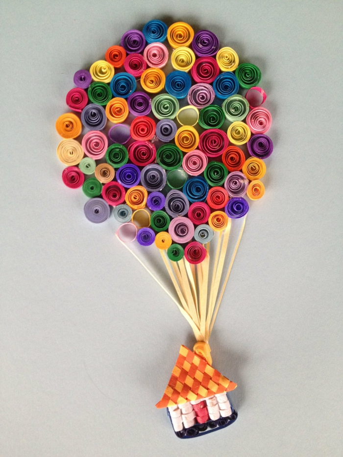montgolifière originale en papier plié, plusieurs rouleaux de papier et une petite maison