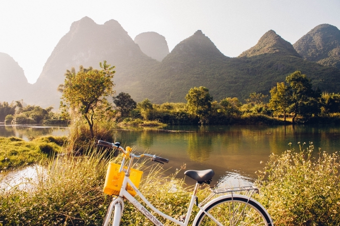 exemple de joli fond d écran avec vélo blanc et noir devant un grand lac et collines de montagnes vertes illuminés par les rayons du soleil