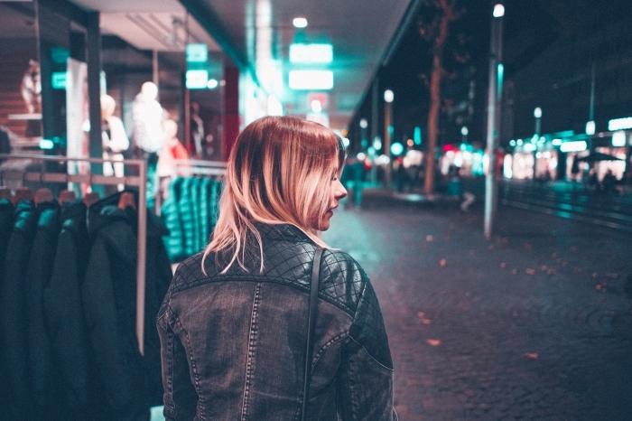 coupe de cheveux femme avec coloration technique ombré blond sur base marron, modèle de veste en cuir et tissu foncé