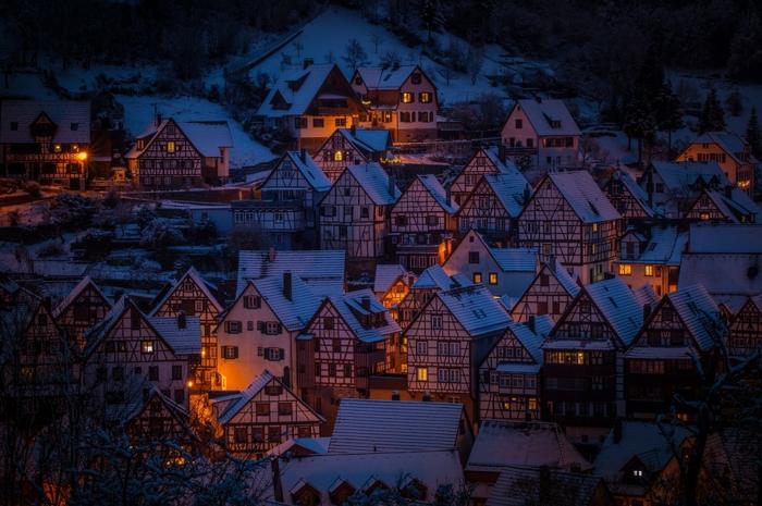 un village dans les Alpes allemandes, tombée du soir, maisons en style chalets illuminés par des lumières douces, sommet recouvert de neige