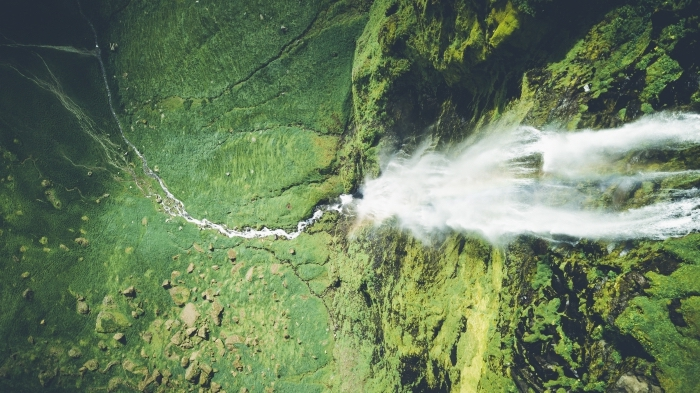 photo de la nature d'en haut pour un fond d écran zen, vue d'oeil d'oiseau avec rochers chute d'eau et champs verts