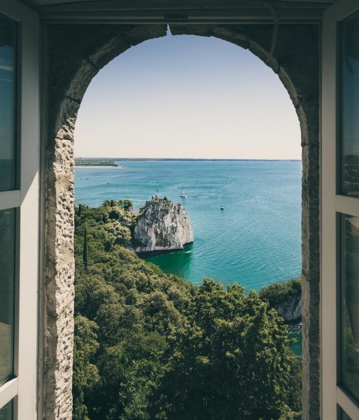 image fond d écran, vue par la fenêtre vers eau turquoise et rochers sur un ile, paysage spectaculaire pour wallpaper ordinateur