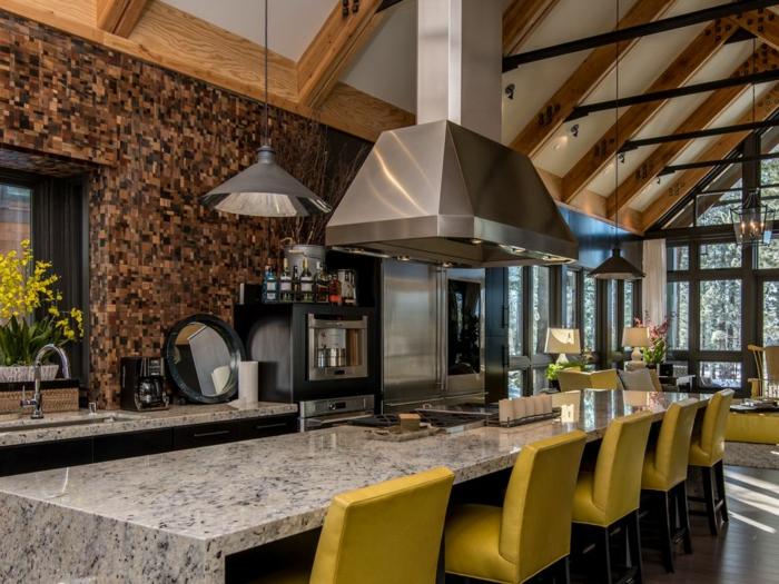 cuisine design loft dans une maison moderne, grande table en granit, lampe industrielle, chaises jaunes