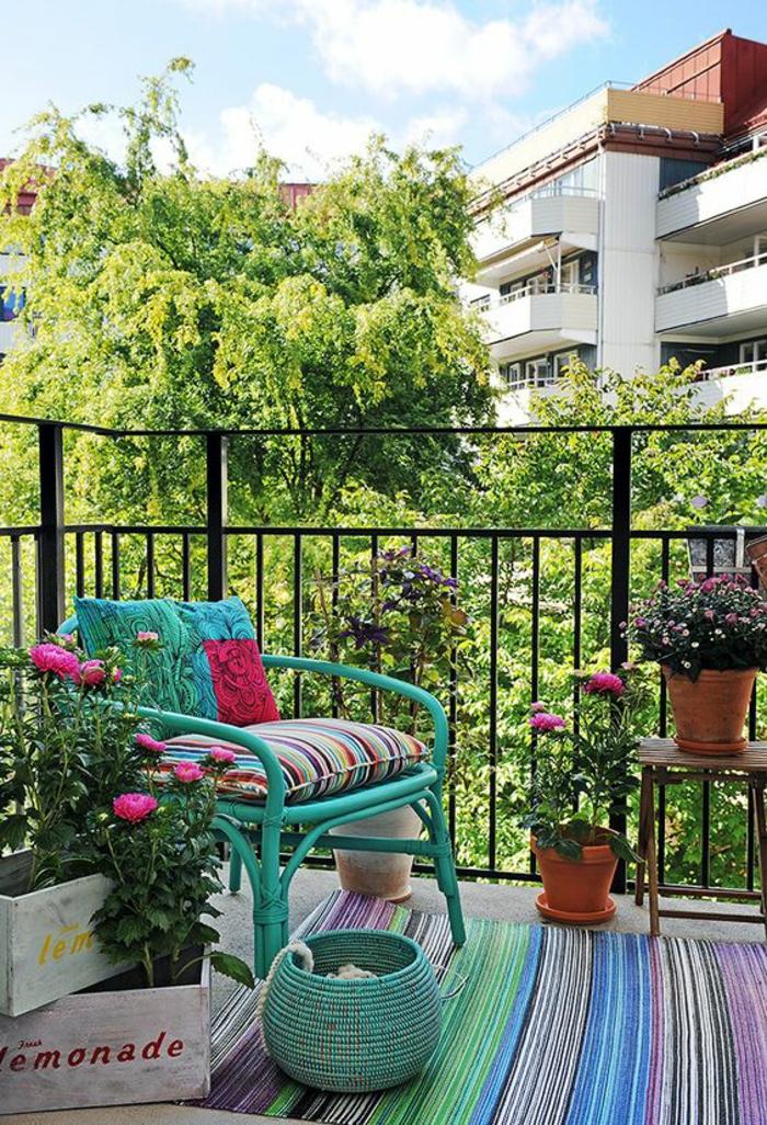 magnifique vue d'une terrasse, idée déco terrasse, idee amenagement terrasse, fauteuil en canne en vert lac, panier tressé en vert lac, tapis ethnique en vert, jaune, bleu indigo, palettes avec des fleurs