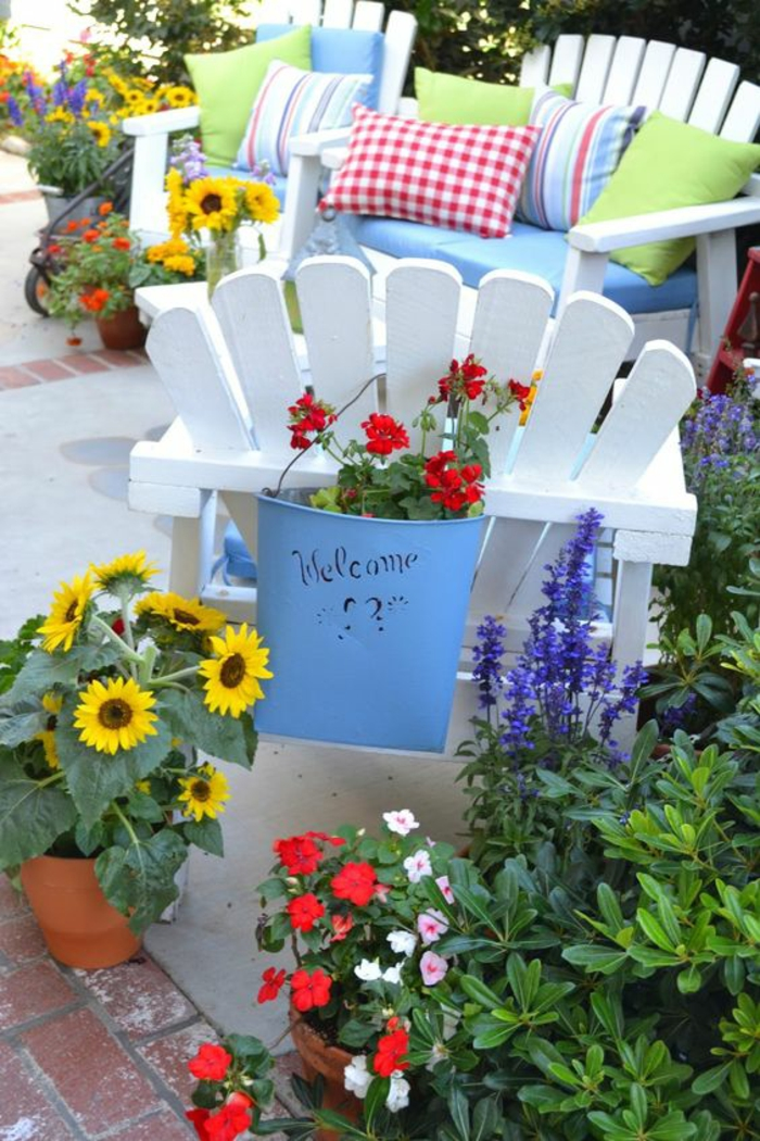 decorer son jardin, idee amenagement jardin devant maison, meubles en bois blanc avec des coussins multicolores, aménagement jardin pas cher