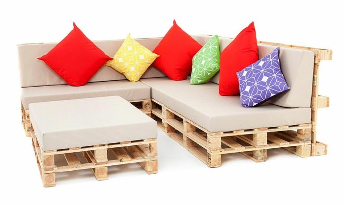 canapé palette avec des coussins carrés en couleur ivoire, coussins carrés en rouge, vert pomme, jaune et lila, table de jardin en palette