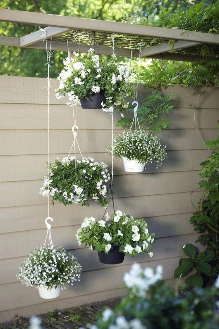 décorer son jardin avec des pots de plantes suspendus, ambiance féerique, coin avec pergola, cintre en couleur blanc crème, amenagement exterieur