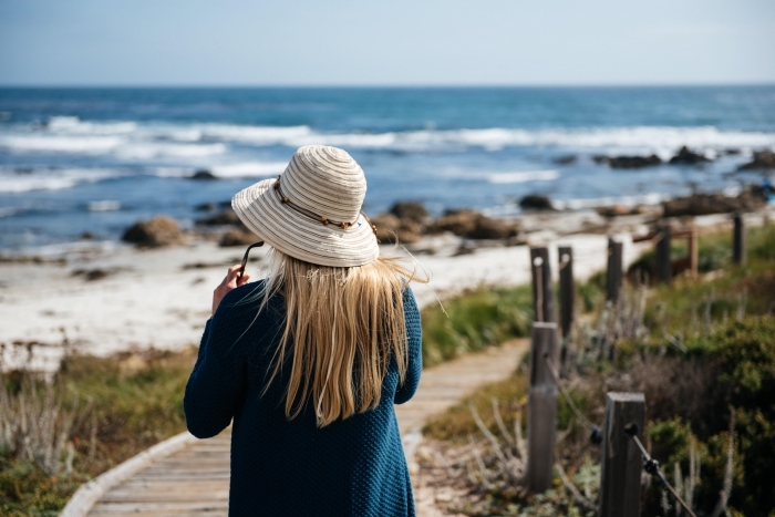 jeune femme en promenade au bord de l'océan habillée en gilet en crochet bleu foncé avec accessoires tendance capeline et lunettes de soleil