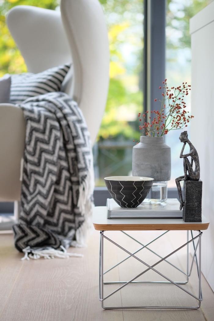 coin de repos aménagé avec un fauteuil de cuir blanc couvert avec coussin et plaid à design rayé et une petite table décorée avec objets