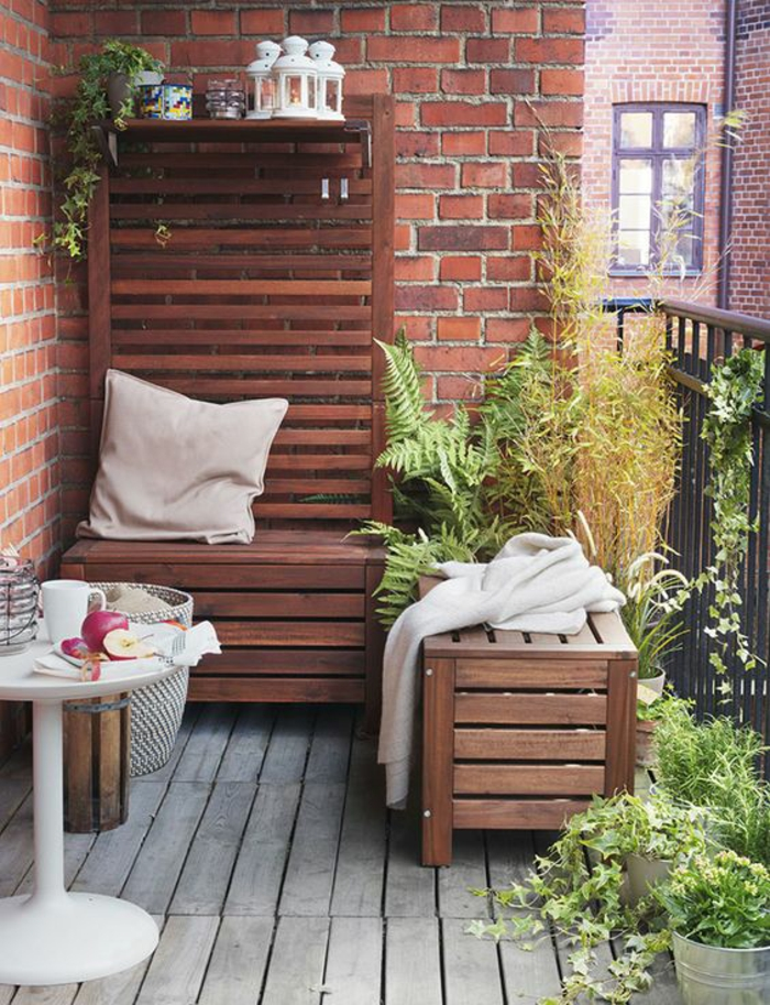 idee deco terrasse, mur en briques rouges, sol en bois de palettes grises, table ronde en plastique blanche, fauteuil deux places et tabouret en palettes