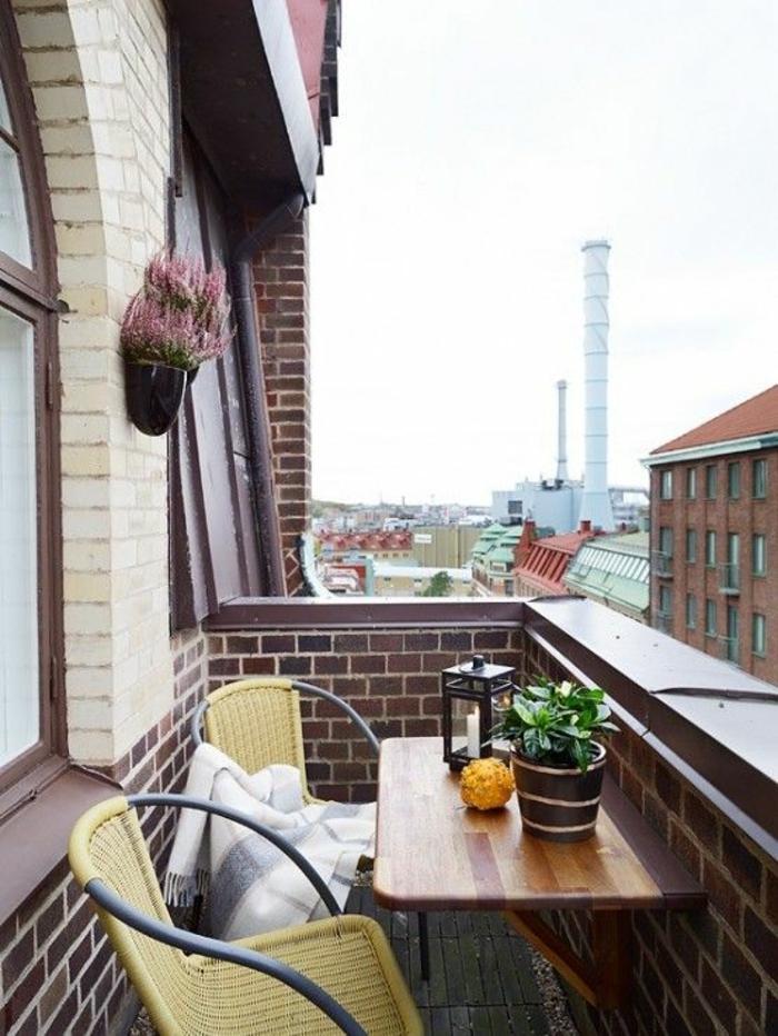 deux chaises en métal noir et en plastique jaune, table pliable, decoration terrasse exterieur, idée déco terrasse, vue sur un établissement en briques rouges, ambiance nordique