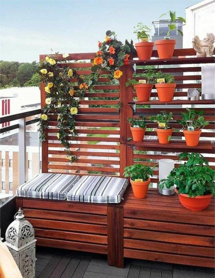 balcon fleuri avec mur aux pots de plantes, idee deco terrasse, meubles en palettes peintes et laquées, lanterne en métal blanc, garde-corps terrasse en verre trempé transparent