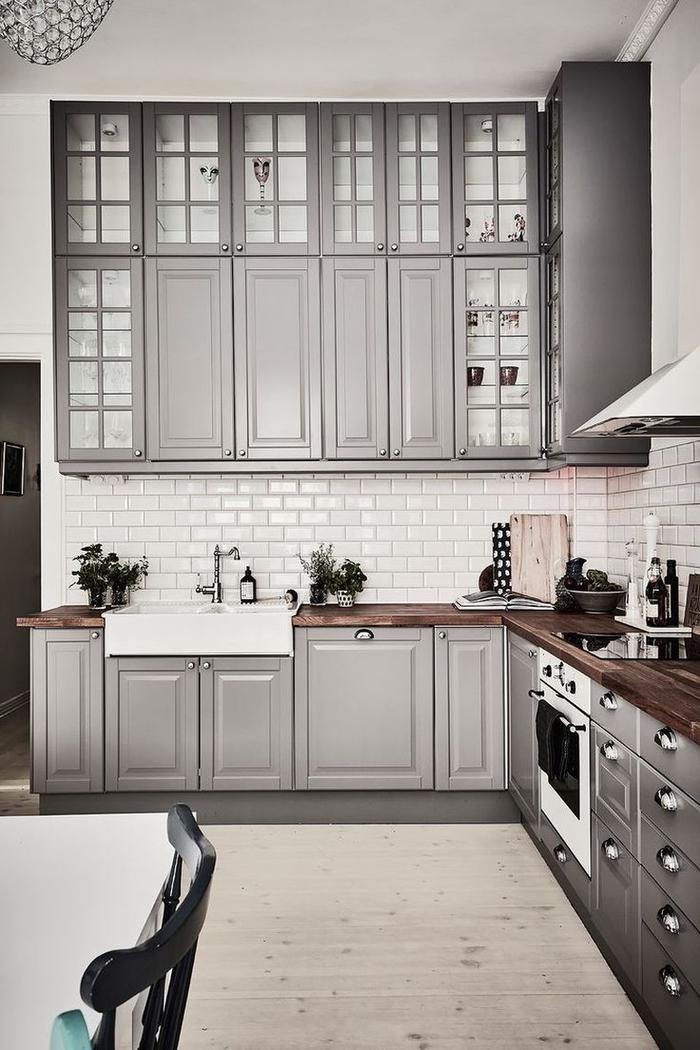 une cuisine conviviale et chic aux placards hauts jusqu'au plafond avec des portes vitrées, couleur pour une cuisine gris taupe tendance