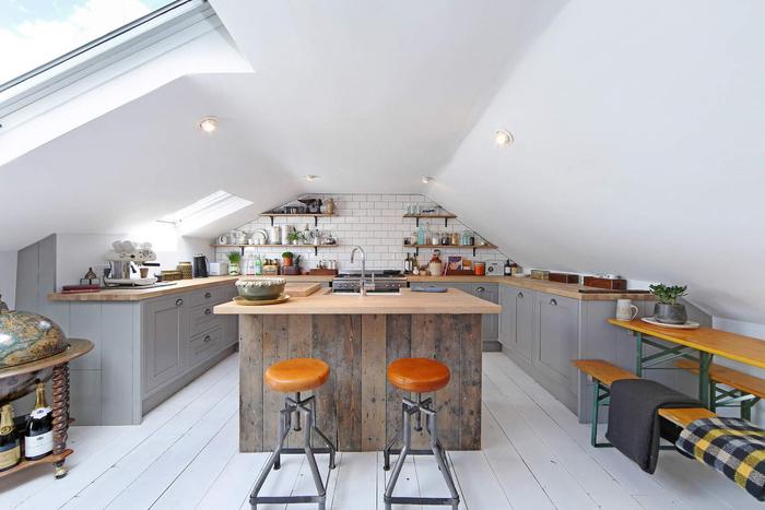 une cuisine grise et bois d'esprit scandinave industriel aménagée sous combles, équipée d'un îlot central revêtu de bois de grange