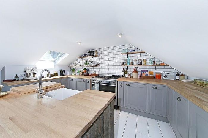 petite cuisine grise et bois aménagée sous combles et agrandie visuellement par le blanc aux murs et au sol
