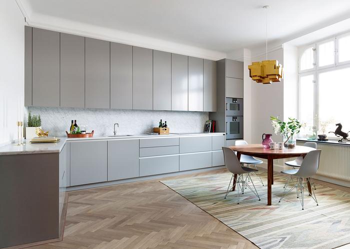 une cuisine grise et blanche élégante de style scandinave aménagée en l, au design minimaliste avec ses meubles sans poignées