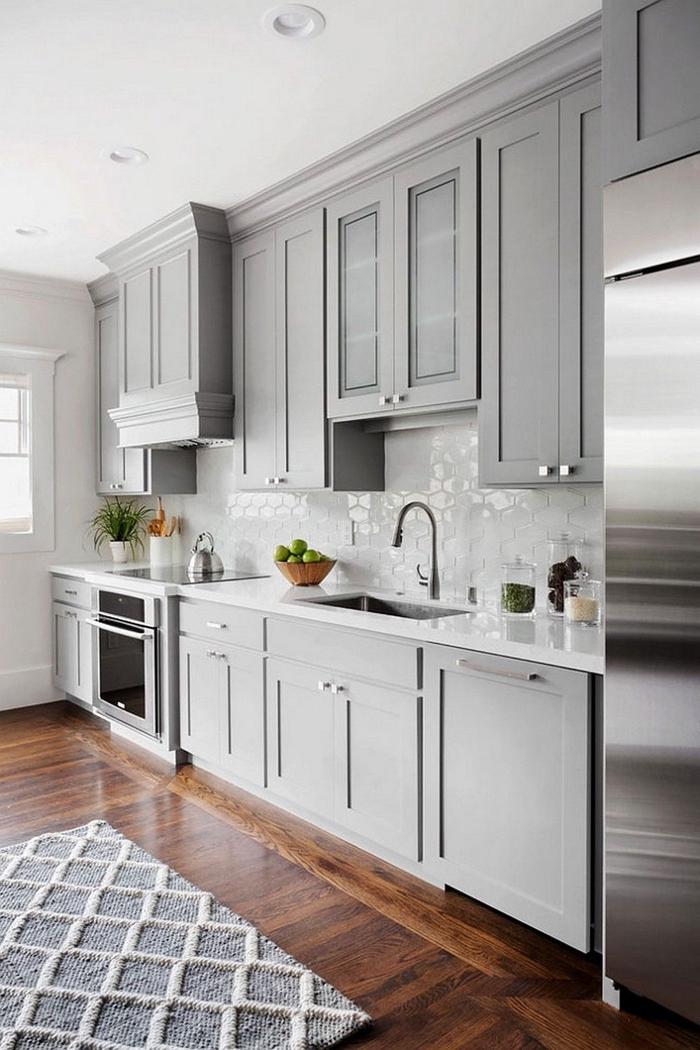 une cuisine grise et blanche aménagée en longueur où la crédence brillante et l'inox s'accordent parfaitement avec la couleur des meubles