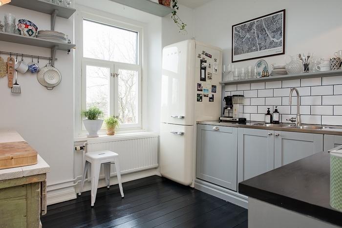 les meubles de hauts sont remplacés par une étagère murale ouverte qui donne un aspect rustique à cette cuisine blanche et grise